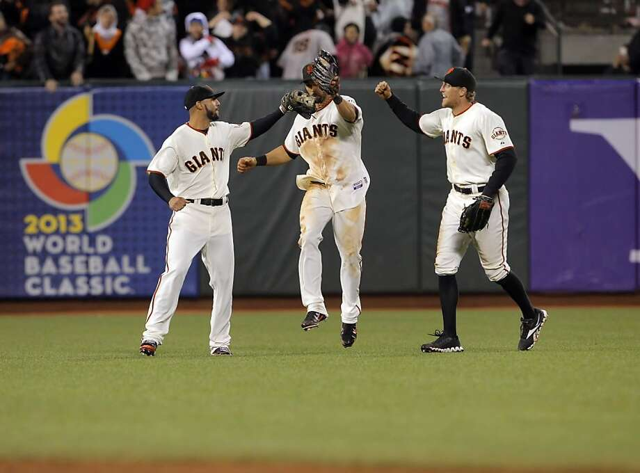 Justin Christian, left, Angel Pagan, center, and Hunter Pence, right, celebrate their victory after the Giants defeated the Rockies 2-1. The San Francisco Giants played the Colorado Rockies at AT&T Park in San Francisco, Calif., on Monday, September 17, 2012. Photo: Carlos Avila Gonzalez - San Fran, The Chronicle
