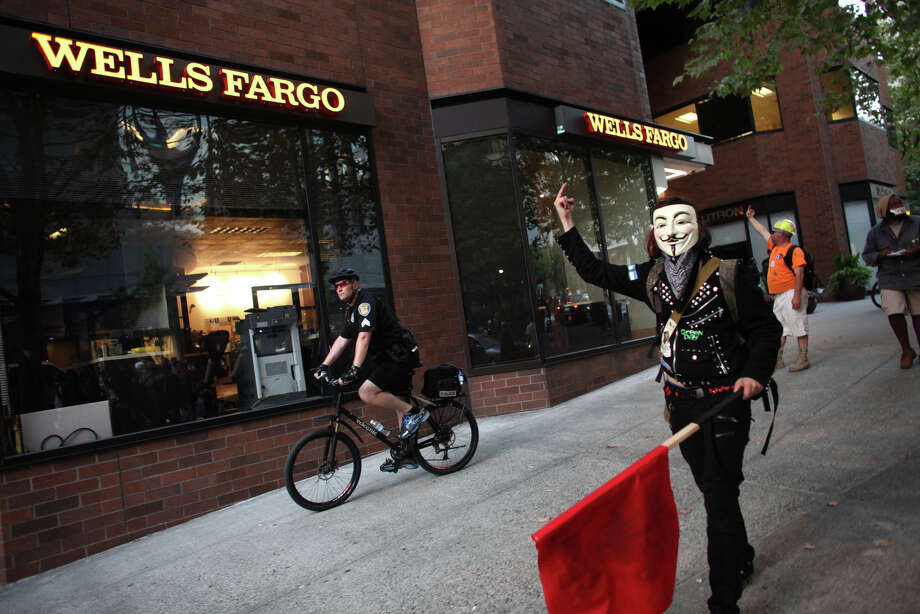 Protesters gesture toward a bank as they silently march on the first anniversary of the Occupy movement on Monday, September 17, 2012 in downtown Seattle. Photo: JOSHUA TRUJILLO / SEATTLEPI.COM