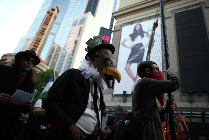 People participate in a silent march during the first anniversary of the Occupy movement in downtown