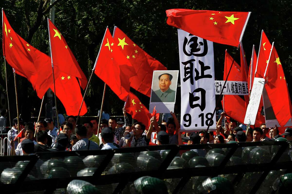 Anti-Japan protesters hold portraits of the late Communist leader Mao Zedong, Chinese national flags, and a poster that reads: