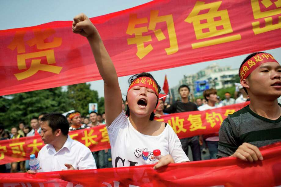 "TOPSHOTS  A Chinese demonstrator shouts slogans during a protest against Japan's ""nationalizing"" of Diaoyu Islands, also known as Senkaku in Japan, in Hangzhou, east China's Zhejiang province, on Septermber 18, 2012.Thousands of anti-Japan protesters rallied across China over a territorial row on September 18, a key historical anniversary, as Japanese firms including car giant Toyota shut or scaled back production.  CHINA OUT    AFP PHOTOSTR/AFP/GettyImages Photo: STR, AFP/Getty Images / AFP"