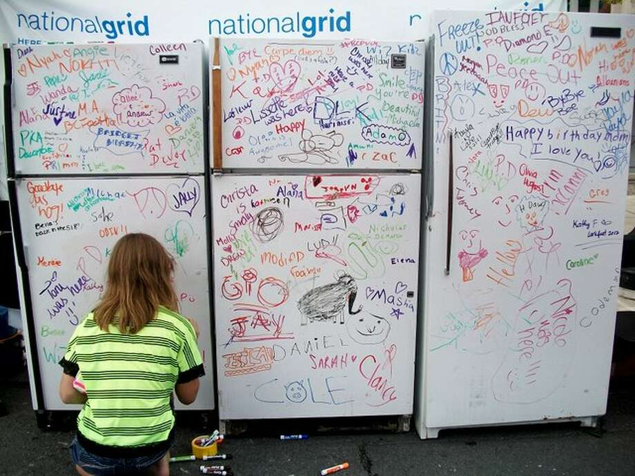 Girl writes a goodbye to old refrigerators at the National Grid tent. Photo by Ariella Phillipo. Photo: Picasa, New Visions: Journalism & Media Studies