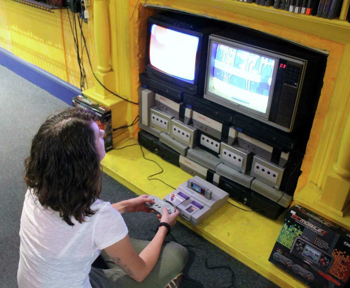 Need to take a break from the hectic street? Just follow Kim Hodgdon of Albany's lead and head into the retro game shop, Pastime Legends, right on Lark Street. Photo by Alex Luciano.