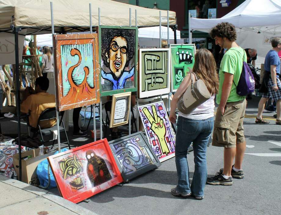 A couple stops to admire one of the many tents displaying art by local artists. Photo by Alex Luciano. Photo: New Visions: Journalism & Media Studies