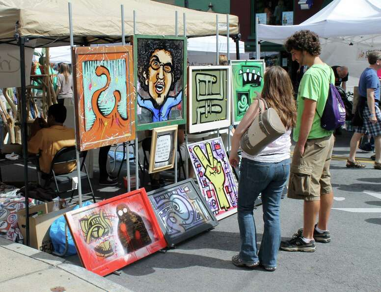 A couple stops to admire one of the many tents displaying art by local artists. Photo by Alex Lucian