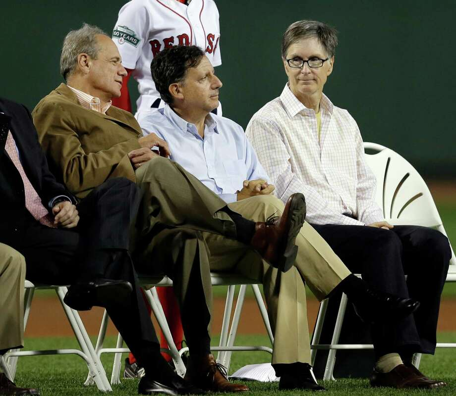 Boston Red Sox owners, from left, Larry Lucchino, Tom Werner and John Henry sit on the field during a ceremony prior to a baseball game against the New York Yankees at Fenway Park in Boston Wednesday, Sept. 12, 2012. The Red Sox have expressed interest in hosting a UConn-Notre Dame football game at Fenway Park in 2014. (AP Photo/Elise Amendola) Photo: Elise Amendola, Associated Press / AP