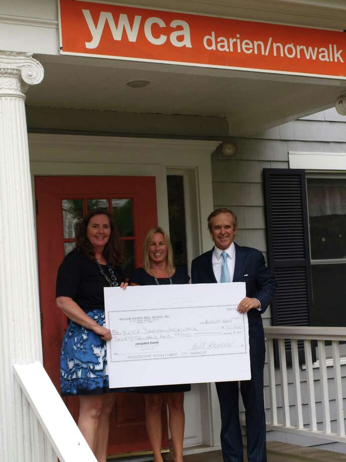 Ellen Kirby, left, executive director of the YWCA Darien/Norwalk, accepts a $30,000 donation from Deirdre McGovern, director of business development and agent in the William Raveis Darien office, and Bill Raveis, chairman of William Raveis Real Estate, Mortgage and Insurance. Photo: Contributed