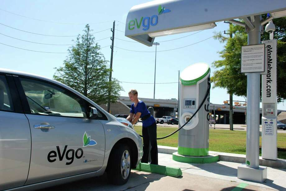 Carly Kade demonstrates how to use new technology to charge an electric vehicle. A fully charged battery can take the cars around 100 miles. Photo: Lindsay Peyton