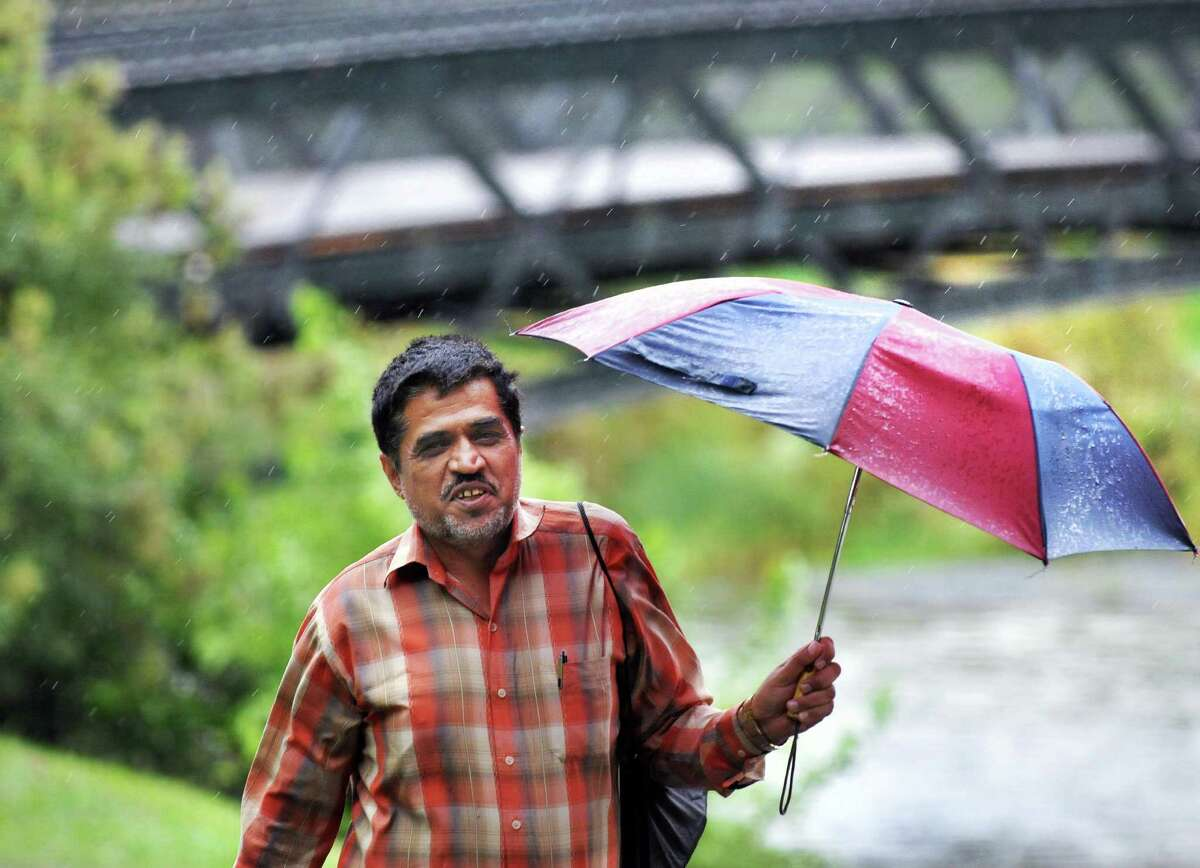 Del Safi gets little protection from a small umbrella Tuesday as he walks through Washington Park in Albany. (John Carl D'Annibale / Times Union)
