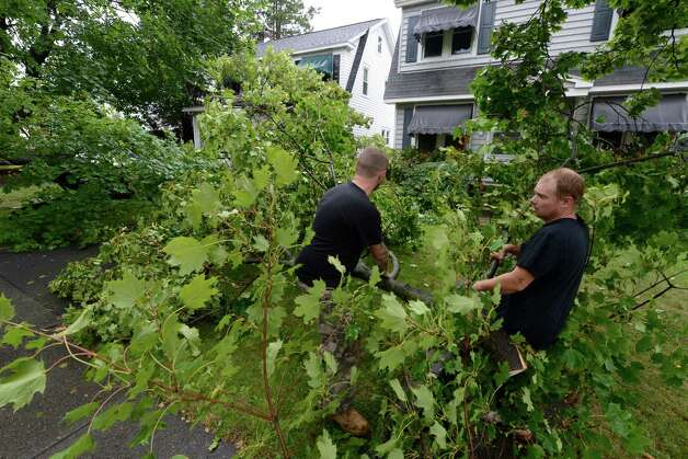 Michael Chamberlain, left, and Shane Davis help remove tree branches Tuesday from the front of 62 Edgecomb St. in Albany.  (Skip Dickstein / Times Union) Photo: Skip Dickstein