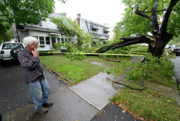 Homeowner Donald Nardacci, left, looks over the damage to the front of his house Tuesday at 62 Edgecomb St. in Albany. (Skip Dickstein / Times Union) Photo: Skip Dickstein