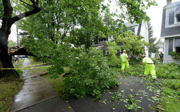 Members of the Albany City Forestry Service remove tree branches Tuesday from the front of 62 Edgecomb St. in Albany.  (Skip Dickstein / Times Union) Photo: Skip Dickstein