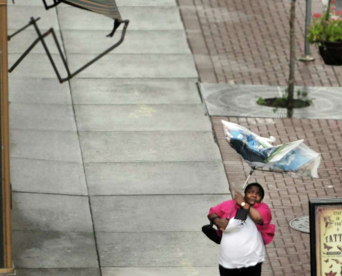 A woman tries to get control of her umbrella in high winds Tuesday along South Pearl Street in Albany. (Paul Buckowski / Times Union)