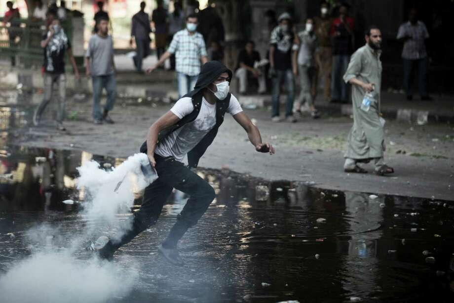 A protester throws a tear gas canister back at police during clashes going on for a third straight day, Thursday in Cairo, Sept. 13, 2012. For all the harrowing images of the deadly attack on the American mission in Benghazi, Libya, and the American Embassy in Cairo coming under siege from protesters Tuesday, the Obama administration is grappling with the possibility that its far bigger long-term problem lies in Egypt, not Libya. Photo: TARA TODRAS WHITEHILL, New York Times / NYTNS
