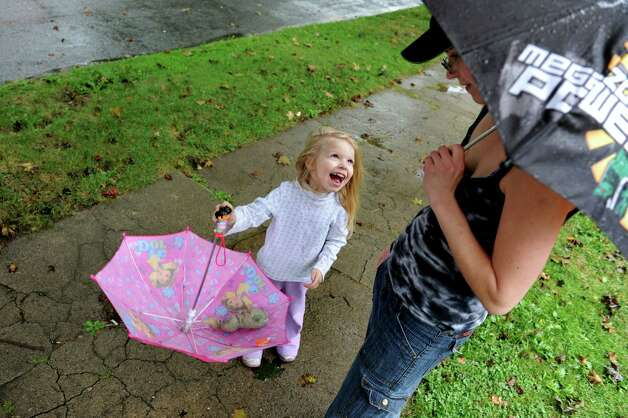 Zoey Whitman, 4, of Mechanicville plays with her umbrella under  the watchful eye of her mother, Jessica Layton-Whitman, on Tuesday, Sept. 18, 2012, in Mechanicville, N.Y. Zoey was waiting for the school bus to bring home her older siblings. (Cindy Schultz / Times Union) Photo: Cindy Schultz /  00019313A