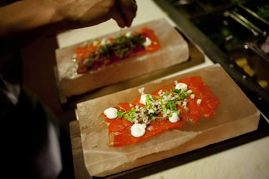 Crudo, raw wild salmon on a Himalayan salt block, is enhanced with sweet pickled green mango, lemon oil, creme fraiche and celery microgreens. Photo: Sonja Och, The Chronicle