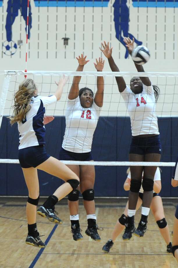Fort Bend Dulles High School visited Fort Bend Clements for a volleyball match.  Dulles won the contest 3-0.   Left, Clements Bradlee Borgfeldt (3) met Dulles defenders, Kristina Mouton (12) and Abolanle Onipede (14) at the net and tried to hit past them. Photo: Eddy Matchette / Freelance