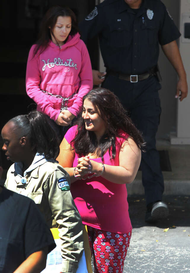 Female suspects in an alleged smuggling ring walk out of the back of the federal courthouse Tuesday September 18, 2012. Wearing the pink top (smiling) and pajama pants is supect April Gaitan and behind her (wearing pink hoodie) is suspect Sonia Campos Delgado. Photo: John Davenport, San Antonio Express-News / San Antonio Express-News
