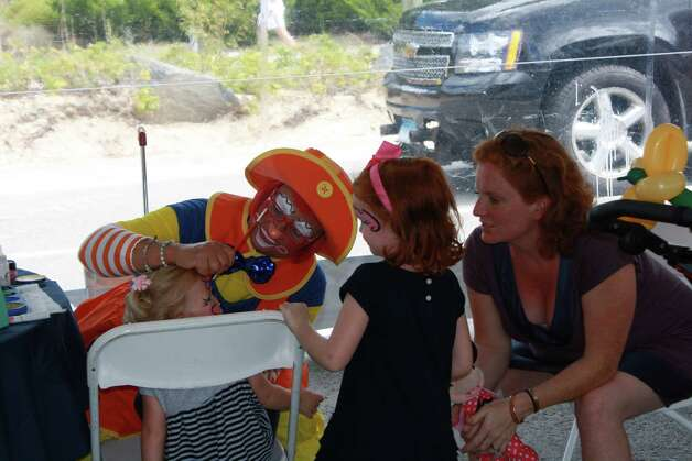 Meghan and Kathleen McDonough watch as Sunburst the Clown (Lynn Discalla) paint Nora McDonough's face at the Darien Road Race on Sept. 16. Sept. 16, 2012. Photo: Megan Davis