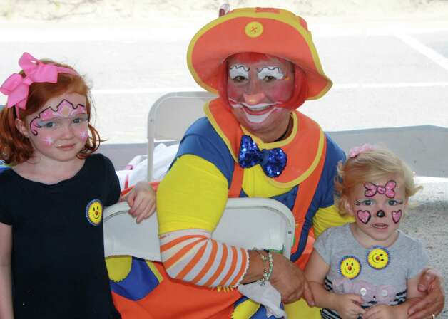 Kathleen McDonough, 5, and Nora McDonough 2, pose with Sunburst the Clown from Humor and Health Assoication at the Darien Road Race on Sept. 16. Sept. 16, 2012 Photo: Megan Davis