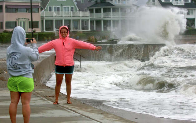 Eryn Mackin, of Milford, snaps a photo of her friend Catherine Eager as waves from Long Island Sound crash into the sea wall behind her along Beach Avenue in the Woodmont section of Milford, Conn. on Tuesday September 18, 2012. Photo: Christian Abraham / Connecticut Post