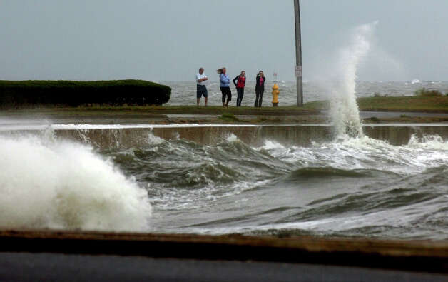 Pedestrians watch waves from the Long Island Sound crash into the sea wall along Beach Avenue in the Woodmont section of Milford, Conn. on Tuesday September 18, 2012. Photo: Christian Abraham / Connecticut Post
