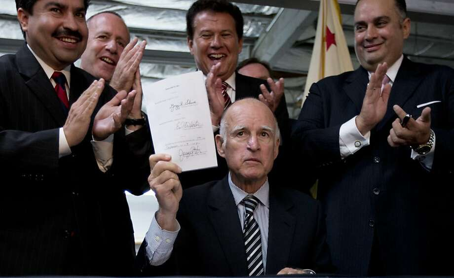 Surrounded by members of the Assembly and state Senate, Gov. Jerry Brown displays the bill he signed, SB863. Supporters say the bill will save businesses $1 billion next year. Photo: Gregory Bull, Associated Press