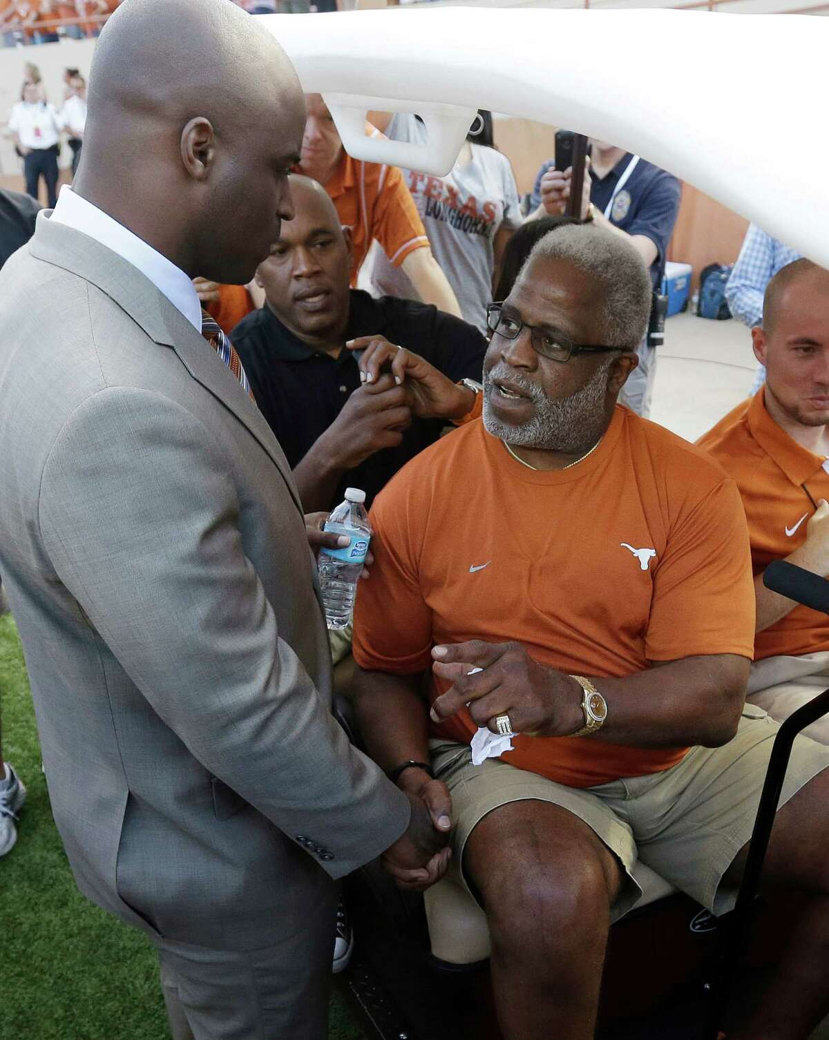 FILE - In this Sept. 8, 2012 file photo, former Texas football player Earl Campbell, right, talks with Ricky Williams, left, as he prepares to take part in the coin flip prior to an NCAA college football game between Texas and New Mexico in Austin, Texas. The NFL Hall of Famer and former Heisman Trophy winner said Tuesday, Sept. 18, 2012, he is undergoing nerve treatment after doctors ruled out concerns that he might have Lou Gehrigís disease. (AP Photo/Eric Gay)