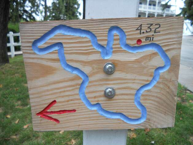 Carved wood signs along Elkhart Lake's walking path show where you are on the path. Image credit Robin Soslow