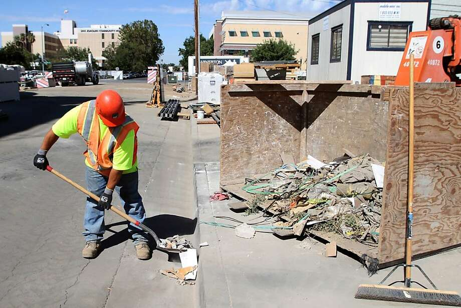 Mike Richards shovels trash at the site of a cancer center under construction in downtown Bakersfield. Photo: Kirk McKoy, McClatchy-Tribune News Service