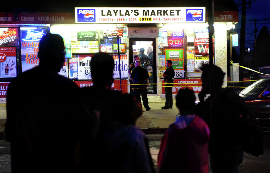A family watches as Bridgeport police officers and detectives investigate at the scene of a shooting, which injured one person, at Layla's Market along Fairfield Avenue in Bridgeport, Conn. on Tuesday September 18, 2012. Photo: Christian Abraham / Connecticut Post