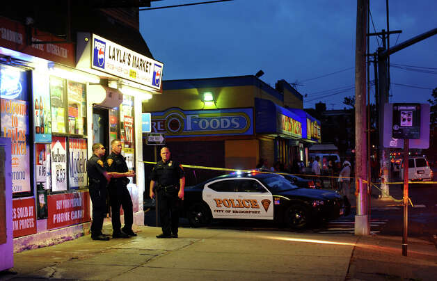 Bridgeport police officers and detectives investigate at the scene of a shooting, which injured one person, at Layla's Market along Fairfield Avenue in Bridgeport, Conn. on Tuesday September 18, 2012. Photo: Christian Abraham / Connecticut Post