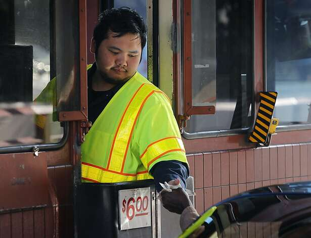 Part-time toll taker Barry Chen collects $6 from a commuter. Photo: Paul Chinn, The Chronicle