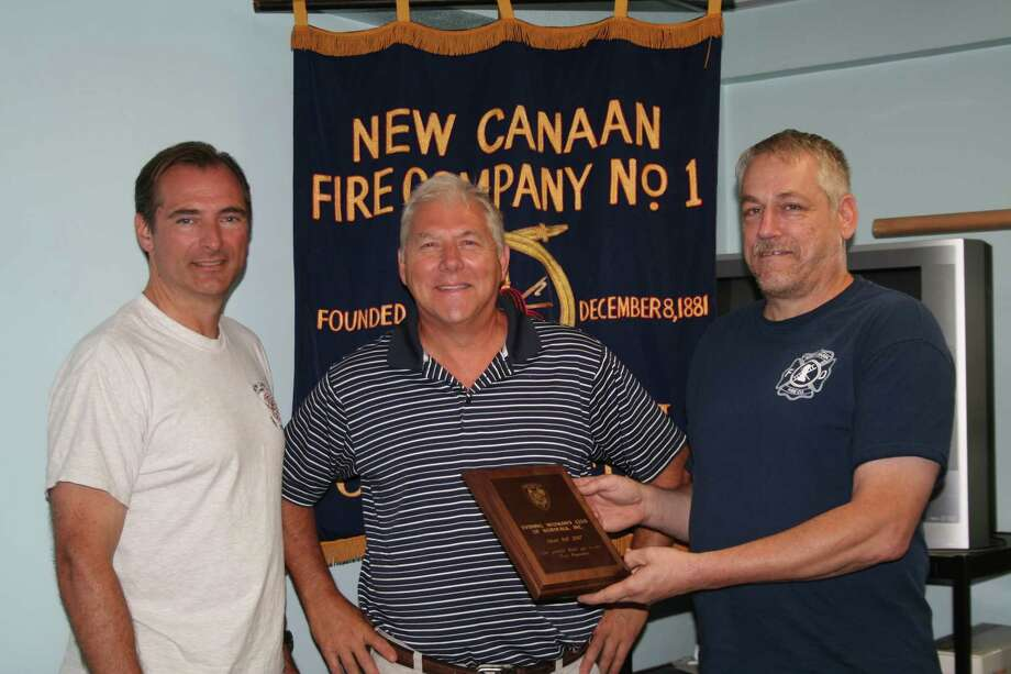 Kerry Smith, left, and New Canaan Fire Chief Edward Karl, right, welcome Tim Brown as an honorary member of the New Canaan Fire Company. Photo: Contributed Photo