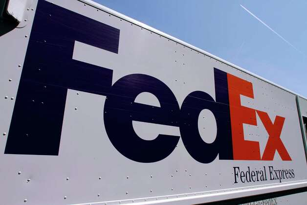 FILE-In this Wednesday, May 16, 2012, file photo, a FedEx delivery truck is seen at the Illinois State Capitol in Springfield, Ill. FedEx Corp. says the global economy is worsening and it's cutting its forecast for the fiscal year ending in May. The world's second largest package delivery company says profit in the current quarter will be well below year ago results.  (AP Photo/Seth Perlman, File) Photo: Seth Perlman
