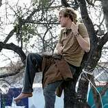 A supporter of Democratic presidential hopeful Sen. Barack Obama, D-Ill., watches from a tree during a town hall meeting in San Antonio, Tuesday, Feb. 19, 2008.