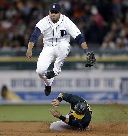 Detroit Tigers shortstop Jhonny Peralta jumps to avoid Oakland Athletics' Cliff Pennington after making the throw to first base to complete a double play on a Chris Carter ground ball in the fourth inning of a baseball game in Detroit on Tuesday, Sept. 18, 2012. (AP Photo/Paul Sancya) Photo: Paul Sancya, Associated Press