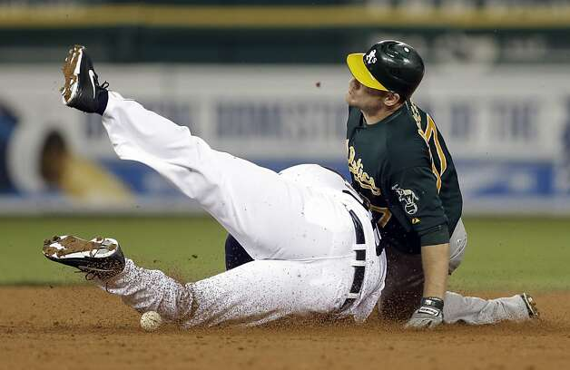 Oakland Athletics' Brandon Moss, right, slides safely into second base for a double as Detroit Tigers first baseman Prince Fielder slides into him trying to catch the ball and make a play in the fifth inning of a baseball game in Detroit on Tuesday, Sept. 18, 2012. (AP Photo/Paul Sancya) Photo: Paul Sancya, Associated Press