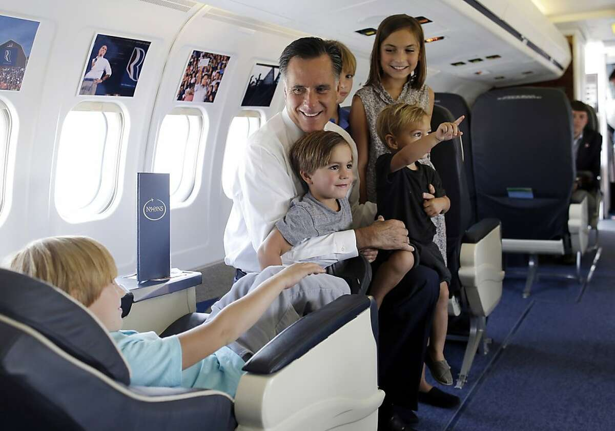 Republican presidential candidate and former Massachusetts Gov. Mitt Romney shows his grandchildren, from left to right: Owen, 5, Nash, 3, Wyatt, 7, Gracie, 9, and Sawyer, 1, his campaign charter plane in Salt Lake City, Tuesday, Sept. 18, 2012. (AP Photo/Charles Dharapak)