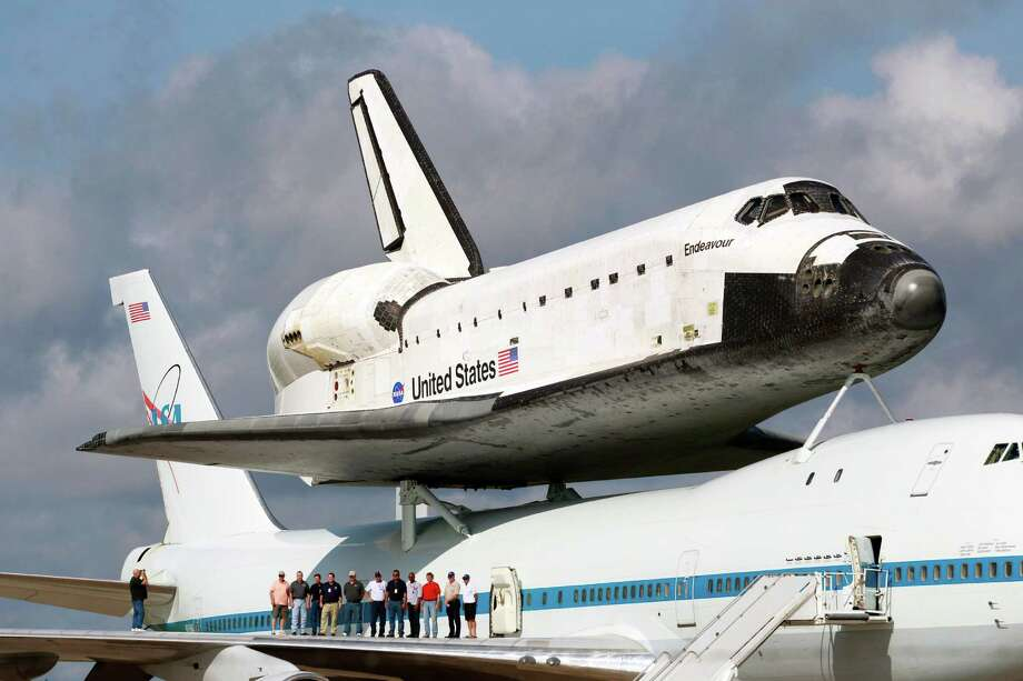 Kennedy Space Center employees pose for a photo Tuesday in front of the Endeavour atop a modified jumbo jet before it was moved to the mate/demate structure for protection from a forecast storm in Cape Canaveral, Fla. Photo: John Raoux / AP