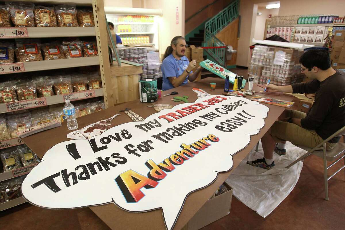 Trader Joe's employees Jason Smith, left and Oliver Wright, right, take time away from stocking shelves to hand paint a few signs at the new Trader Joe's in the Alabama Theater.