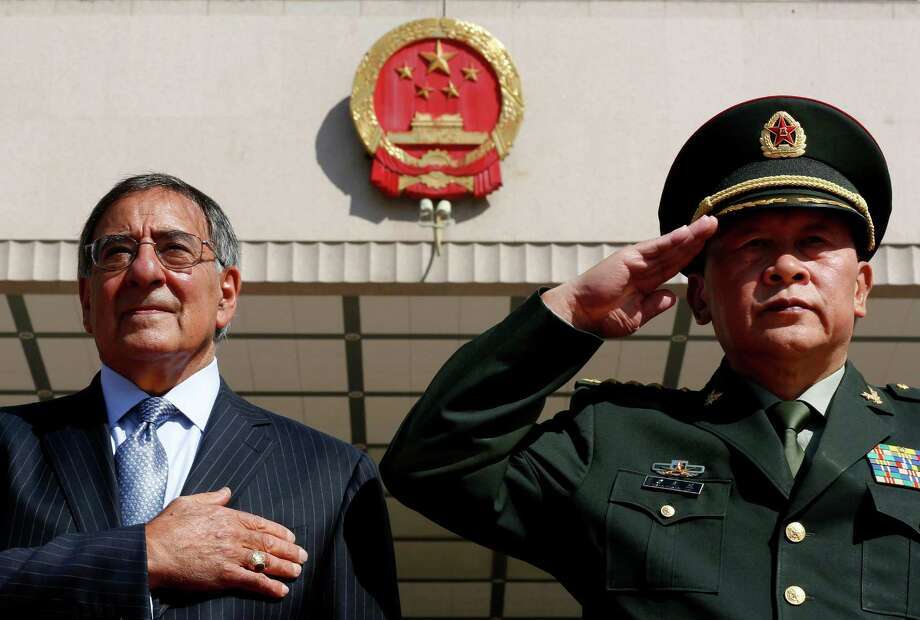 U.S. Defense Secretary Leon Panetta, left, stands at attention during the national anthem next to China's Defense Minister Liang Guanglie at the Bayi Building in Beijing,  China Tuesday, Sept. 18, 2012. (AP Photo/Larry Downing, Pool) Photo: Larry Downing