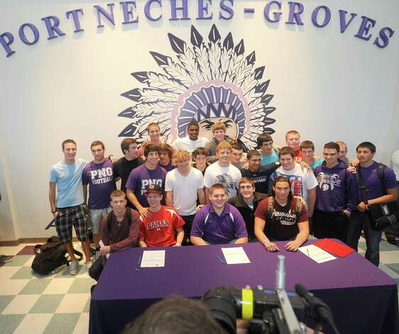 Jayce Nelson, left, and Kyler Nicotre, center pose with teammates and friends after signing their papers Wednesday afternoon during a signing celebration ceremony at the school. Dave Ryan/The Enterprise Photo: Dave Ryan