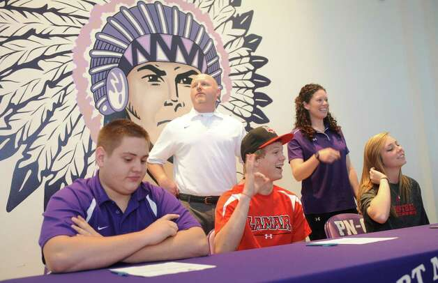 With Port Neches-Groves head football coach Brandon Faircloth behind him, Jayce Nelson, center, flashes to the students, friends, and teachers that were there to watch.  He, along with Kyler Nicotre, left, and Britnee Moore, right, signed their papers Wednesday afternoon during a signing celebration ceremony at the school. Dave Ryan/The Enterprise Photo: Dave Ryan