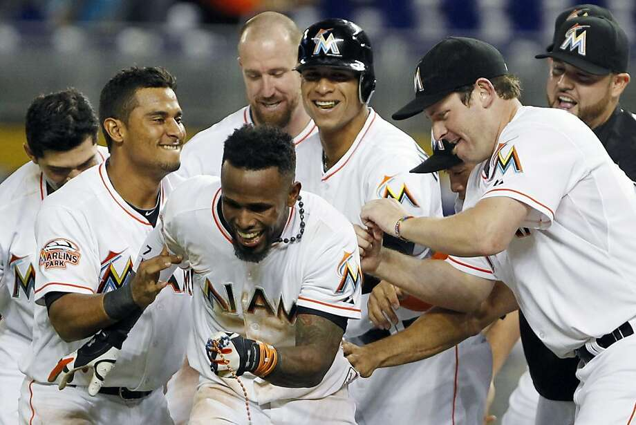 Teammates congratulate Miami Marlins' Jose Reyes, foreground, after Reyes hit a two-out RBI single to defeat the Atlanta Braves 4-3 during the 10th inning. Photo: Wilfredo Lee, Associated Press