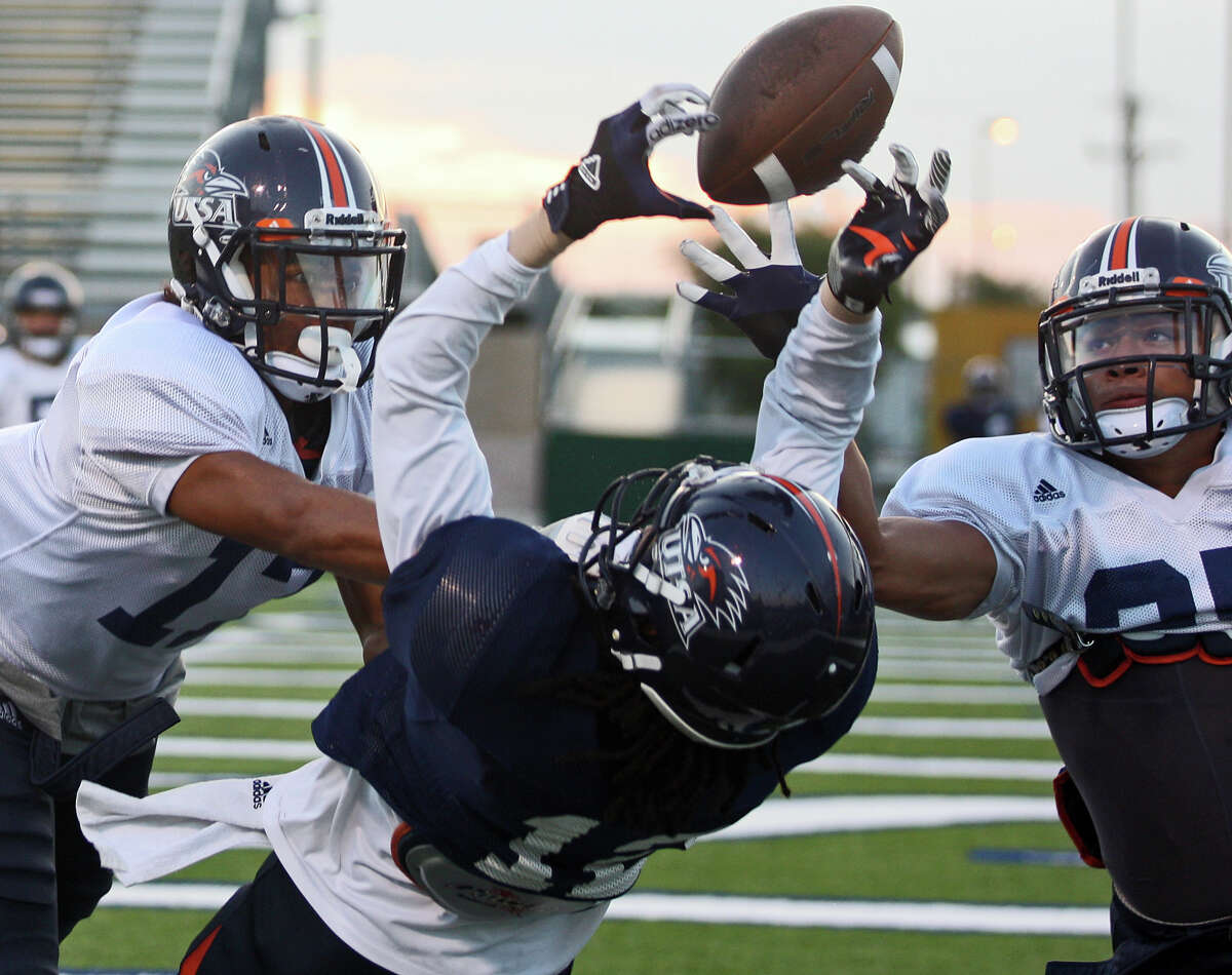 Erik Brown, left, and Maricio Sanchez, right, break up a pass intended for Earon Holmes during University of Texas at San Antonio football team practice at Farris Stadium, Tuesday, Sept. 18, 2012. UTSA is 3-0 for the season.