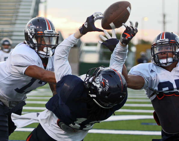 Erik Brown, left, and Maricio Sanchez, right, break up a pass intended for Earon Holmes during University of Texas at San Antonio football team practice at Farris Stadium, Tuesday, Sept. 18, 2012. UTSA is 3-0 for the season. Photo: Jerry Lara, San Antonio Express-News / © 2012 San Antonio Express-News