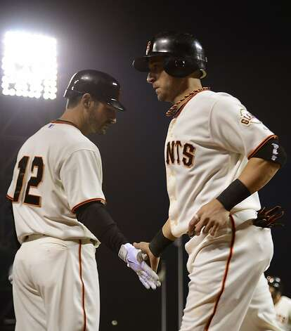 SAN FRANCISCO, CA - SEPTEMBER 18:  Marco Scutaro #19 of the San Francisco Giants is congratulated by Xavier Nady #12 after Scutaro scored in the third inning against the Colorado Rockies at AT&T Park on September 18, 2012 in San Francisco, California.  (Photo by Thearon W. Henderson/Getty Images) Photo: Thearon W. Henderson, Getty Images