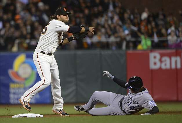SAN FRANCISCO, CA - SEPTEMBER 18:  Brandon Crawford #35 of the San Francisco Giants gets his throw off to complete the double-play while avoiding the slide of Josh Rutledge #14 of the Colorado Rockies in the seventh inning at AT&T Park on September 18, 2012 in San Francisco, California.  (Photo by Thearon W. Henderson/Getty Images) Photo: Thearon W. Henderson, Getty Images
