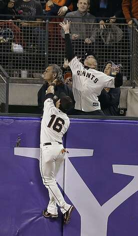 A fan reaches for a two-run home run ball by Colorado Rockies' Wilin Rosario as San Francisco Giants center fielder Angel Pagan (16) watches during the eighth inning of a baseball game on Tuesday, Sept. 18, 2012 in San Francisco. (AP Photo/Marcio Jose Sanchez) Photo: Marcio Jose Sanchez, Associated Press